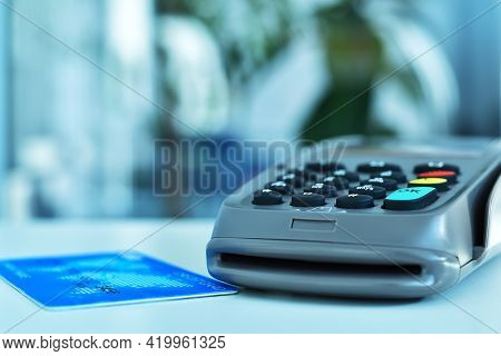 Pos Terminal With Blue Credit Card On Table. Payment With Credit Card On Pos Terminal. Close Up