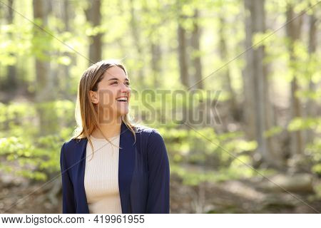 Happy Woman Contemplating Views And Laughing In A Beautiful Forest