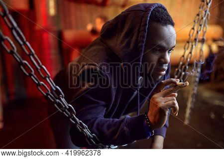 Drug addict man smokes a cigarette in den