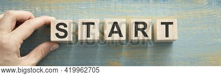 Start Now Or Later Symbol. Businessman Turns Wooden Cubes And Changes Words 'start Later' To 'start'