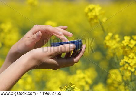 Close Up Of A Woman Hand Holding Moisturizer Jar In A Yellow Field In Spring Season