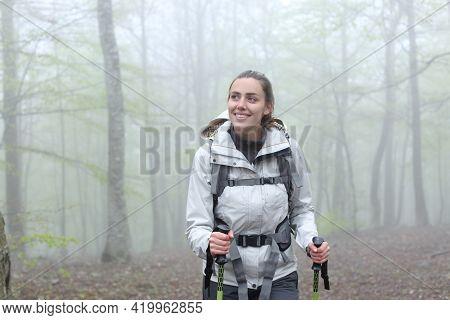 Front View Portrait Of A Happy Trekker Walking In A Foggy Forest
