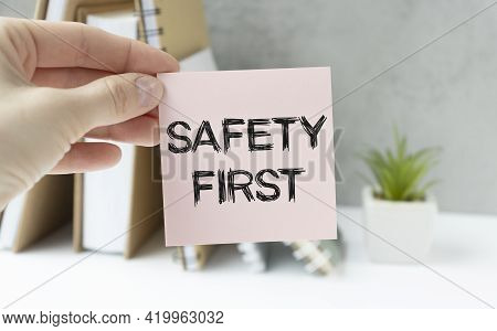 Safety First In Unsafe Workplace Concept Photo. Hand Of Staff Is Holding The Text Sign With Blurred
