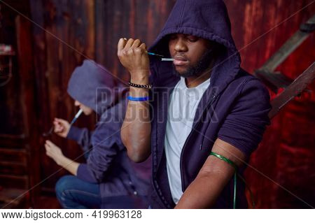 Drug addict man and woman with syringes in den