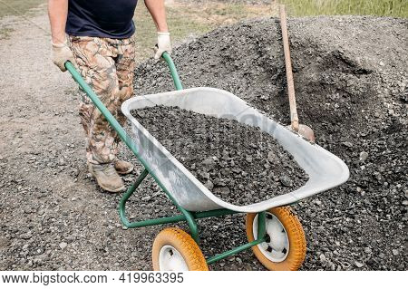 Man Driving A Wheelbarrow With Rubble. As Part Of A Construction Project, A Man Carries Rubble On A