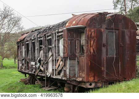 Old And Rusty Abandoned Passenger Wagon, A Carriage Car, Lost And Let To Rot In A Closed Train Stati