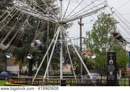 Ripanj, Serbia - May 1, 2021: Swing Ride, Or Chair O Plan, With A Selective Blur On The Employee Sta