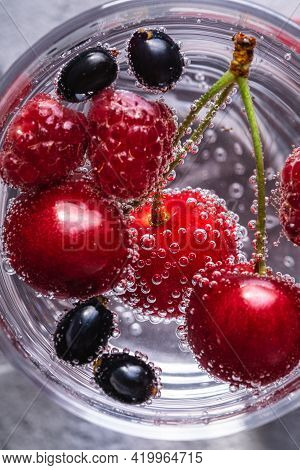 Fresh Cold Sparkling Bubble Water Drink With Cherry, Raspberry And Currant Berries In Transparent Gl