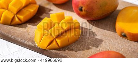 Diced Fresh Mango Fruit On Wooden Cutting Board With Sunlight And Leaf Shadow.