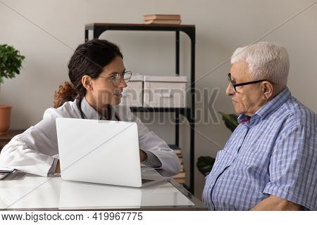 Young Woman Physician Explain Aged Man Therapy Details Using Laptop