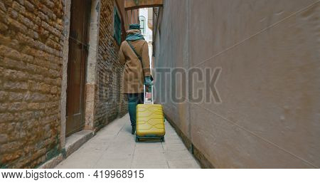 Woman With Trolley Back Walking Along The Alleyway