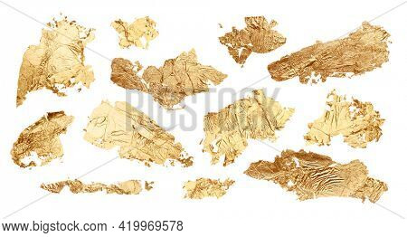 Gold glitter and bronze color blot. Abstract torn piece of metal leaf (potal) paper on white background. Collection.