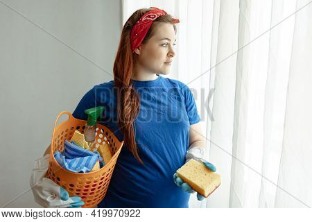 Pregnant Woman With A Basket Of Products For Cleaning The House And Maintaining Cleanliness.
