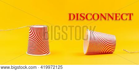 Two Cardboard Red Cups With Strings Lying Apart. Children's Homemade Toy Walkie-talkie. Yellow Backg