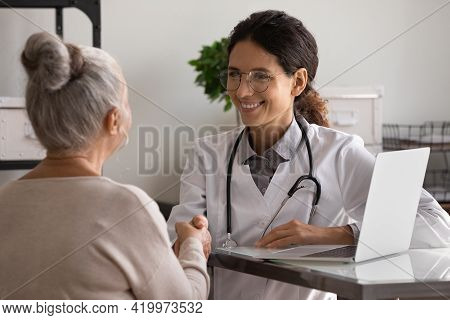 Grateful Aged Female Patient Shake Hand Of Young Woman Doctor