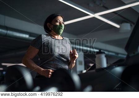 Senior Woman With Face Mask Doing Exercise On Treadmill In Gym, Coronavirus Concept.