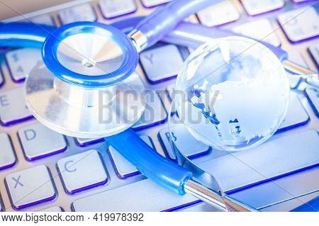 Stetoscope And Blue Glass Globe On Laptop Keyboard - Coronavirus Covid -19 Global Pandemia, Health C
