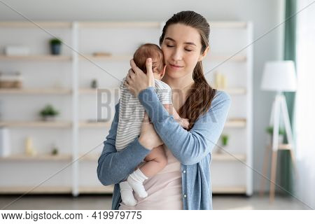 Beeing A Mother. Portrait Of Loving Young Woman Tenderly Embracing Newborn Baby