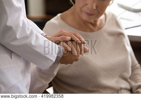 Disabled Senior Female Hand In Palms Of Young Woman Medic