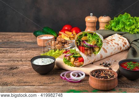 Chicken Shawarma With French Fries, Vegetables, Onions And Lettuce On A Brown Background. Side View,