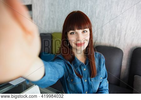 Young Beautiful Redhead Woman Wearing Jeans Shirt, Making Selfie By The Camera With A Happy Face, Si