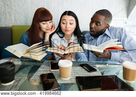Book Lovers, Students, Self-education Concept. Three Surprised Excited Multiethnic Friends, Sitting