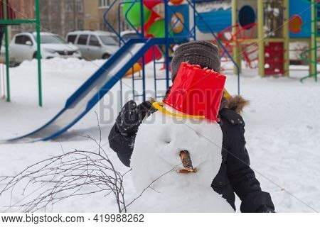 A Boy Is Making A Snowman Out Of Snow In The Winter On The Playground.