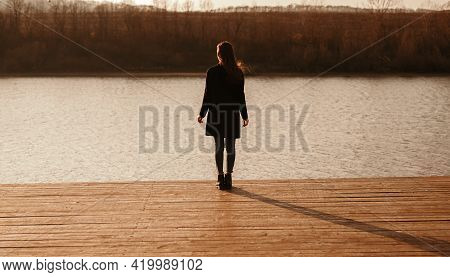 Full Body Back View Of Unrecognizable Female In Black Coat Standing Alone On Wooden Pier Near Calm R