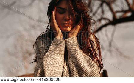 From Below Of Serene Female With Long Hair And Closed Eyes Touching Face At Sundown In Nature