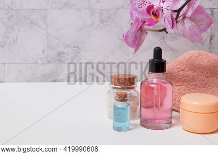 Bottles Of Tincture, Salt, Oil Or Serum, A Towel And A Blooming Orchid Over The Towel In The Bathroo