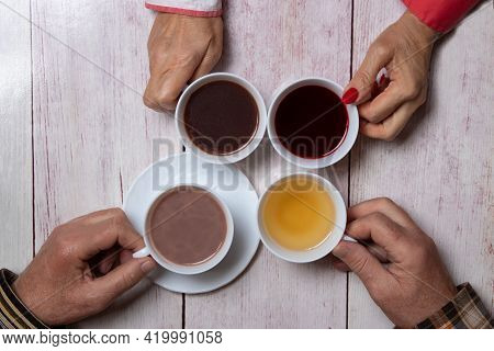 People Drinking Coffee And Tea. Top View Of The Hands Of Four People Drinking Coffee And Tea Togethe