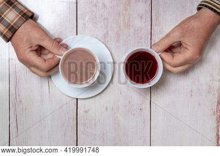 Top View Of Two Hands, One Holding A Cup Of Coffee And The Other Holding A Cup Of Tea On A Rustic Ta