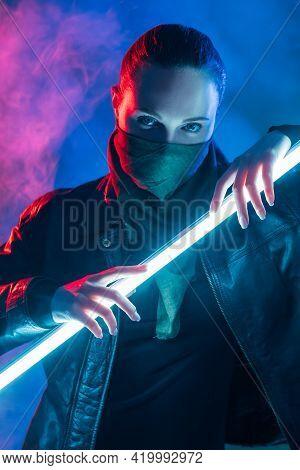 Cyberpunk Portrait. Urban Riot. Future Apocalypse. Red Neon Light Female Hooligan In Face Buff Mask
