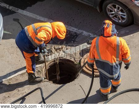 Workers Over The Open Sewer Hatch On A Street. Repair Of Sewage, Underground Utilities, Water Supply