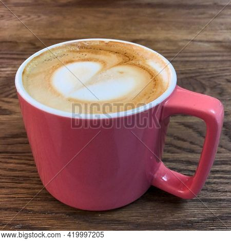 Cappuccino Coffee With A Pattern Of Foam Heart In A Pink Mug