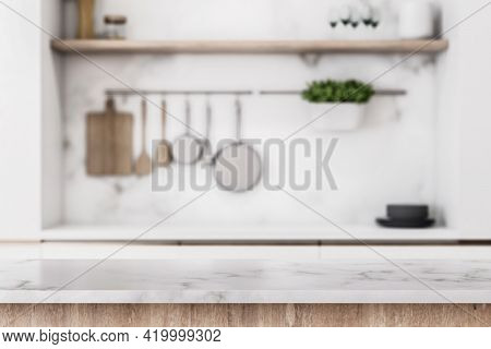 Stylish Marble Tabletop On Wooden Platform With Copyspace For Your Logo At Blurry Kitchen Utensils A