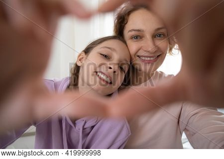 Close Up Teen Girl Showing Heart Sign With Mother.