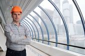 Architect in hard - hat against modern building poster