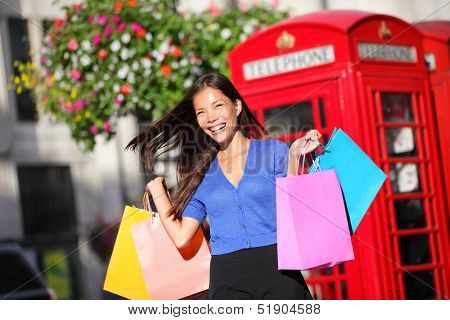 Shopping woman in London walking happy holding shopping bags. Cheerful beautiful multiracial shopper in front of red phone booth. Westminster, London, England, United Kingdom. Asian Caucasian girl.
