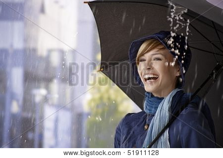 Happy young woman standing under umbrella in rain, laughing.