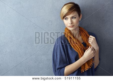 Attractive young woman wearing scarf standing by grey wall, looking away. Copy space.