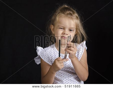 Disheveled girl holding a pair of compasses and a pencil and looks at the compass. Studio, black background. poster
