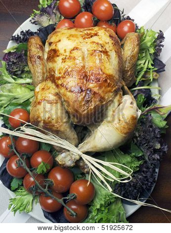 Platter Of Delicious Roast Chicken Turkey With Salad Greens And Red Tomotoes On The Vine For A Succu