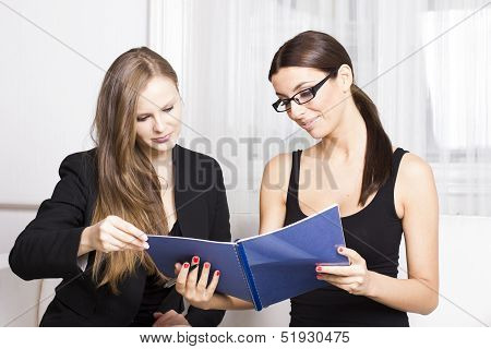 Two beautiful businesswomen having discussion