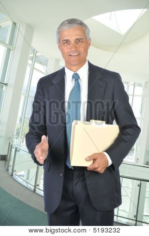 Middle Aged Businessman With File Folder And Hand Extended To Shake