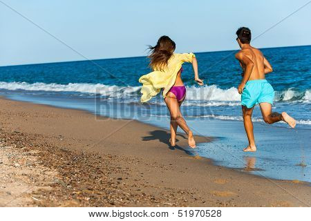 Teen Couple Chasing On Beach.