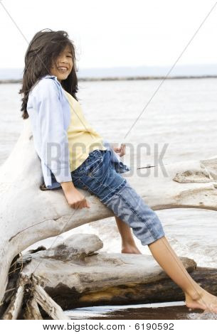 Little Girl Playing On Fallen Tree By Lake Shore In Summer