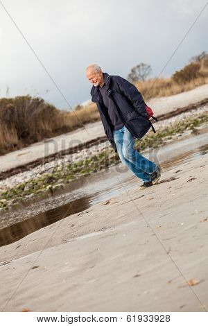 Elderly Energetic Man Running Along A Beach