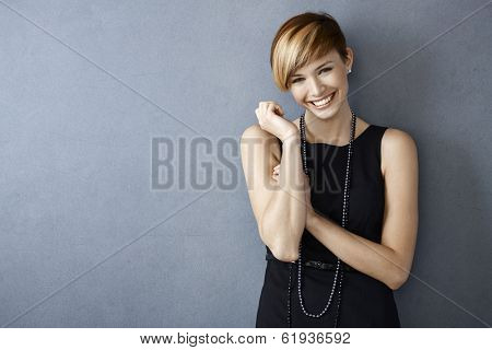 Portrait of happy young woman in black dress and pearls on grey background