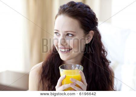 Woman Drinking Orange Juice In Bedroom